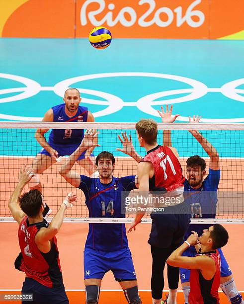 Artem Volvich of Russia and Egor Kliuka of Russia prepare to block the spike of Aaron Russell of United States during the Men's Bronze Medal Match...