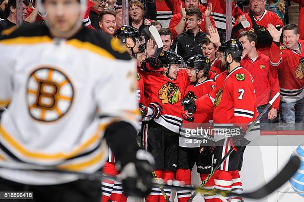 Artemi Panarin and Patrick Kane of the Chicago Blackhawks react after Kane scored his second goal of the NHL game against the Boston Bruins in the...