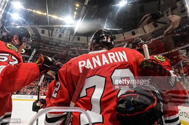 Artemi Panarin of the Chicago Blackhawks celebrates with teammates next to the glass after scoring his second goal in the first period of the NHL...