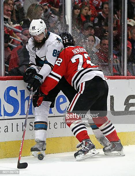 Artemi Panarin of the Chicago Blackhawks checks Brent Burns of the San Jose Sharks into the boards at the United Center on December 20 2015 in...