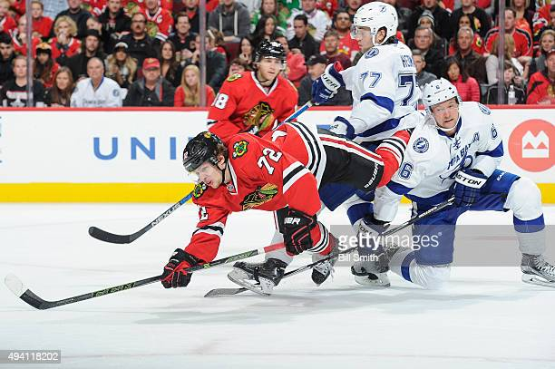 Artemi Panarin of the Chicago Blackhawks falls over Anton Stralman of the Tampa Bay Lightning in the third period of the NHL game at the United...