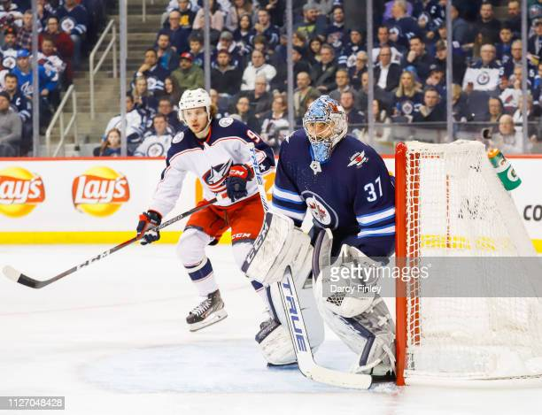 Artemi Panarin of the Columbus Blue Jackets and goaltender Connor Hellebuyck of the Winnipeg Jets keep an eye on the play during third period action...