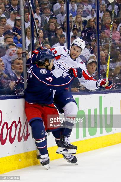 Artemi Panarin of the Columbus Blue Jackets collides with Tom Wilson of the Washington Capitals while chasing after the puck in Game Six of the...