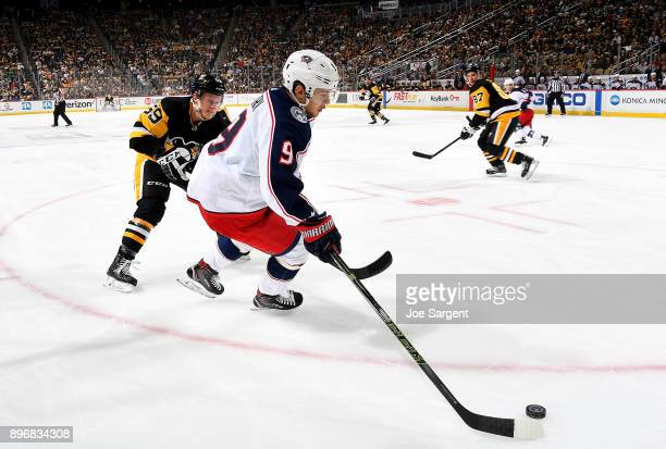 Artemi Panarin of the Columbus Blue Jackets handles the puck against Jake Guentzel of the Pittsburgh Penguins at PPG Paints Arena on December 21 2017...