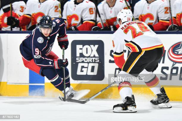 Artemi Panarin of the Columbus Blue Jackets turns the puck away from Travis Hamonic of the Calgary Flames during the first period of a game on...