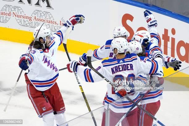 Artemi Panarin of the New York Rangers celebrates with Mika Zibanejad, Chris Kreider, and Ryan Strome after scoring a goal against the Carolina...