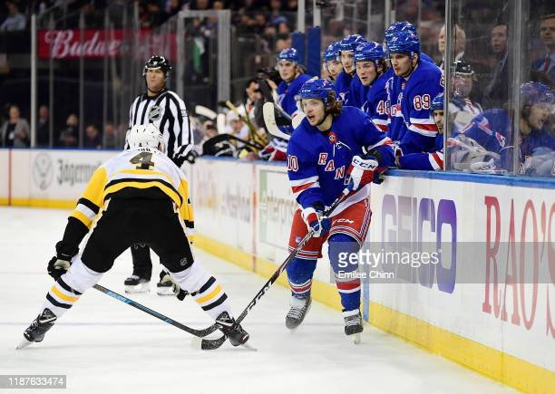 Artemi Panarin of the New York Rangers controls the puck with pressure from Justin Schultz of the Pittsburgh Penguins during their game at Madison...