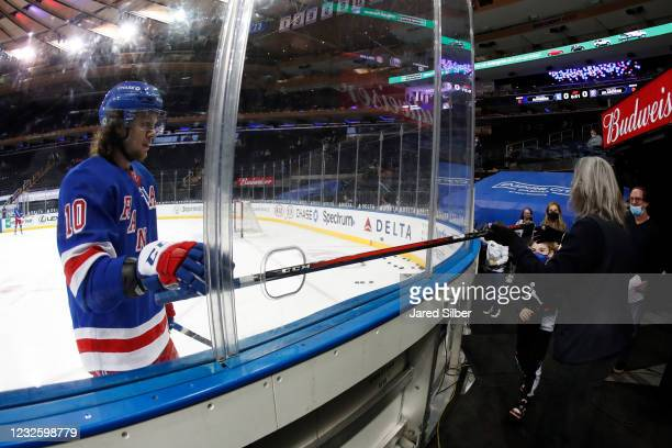 Artemi Panarin of the New York Rangers gives his stick to a young fan during warmups prior to the game against the New York Islanders at Madison...