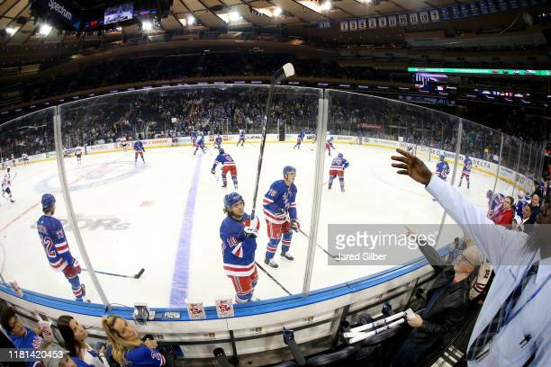 Artemi Panarin of the New York Rangers hands a stick to an employee for a young fan in the crowd during warmups prior to the game against the Florida...