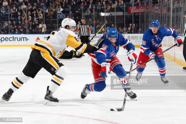 Artemi Panarin of the New York Rangers skates with the puck against John Marino of the Pittsburgh Penguins at Madison Square Garden on November 12...