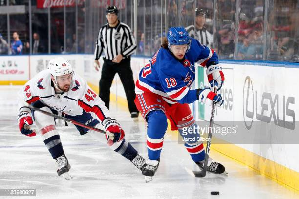 Artemi Panarin of the New York Rangers skates with the puck against Tom Wilson of the Washington Capitals at Madison Square Garden on November 20...