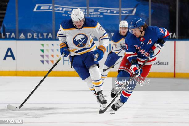 Artemi Panarin of the New York Rangers skates with the puck against Casey Mittelstadt of the Buffalo Sabres at Madison Square Garden on April 25,...