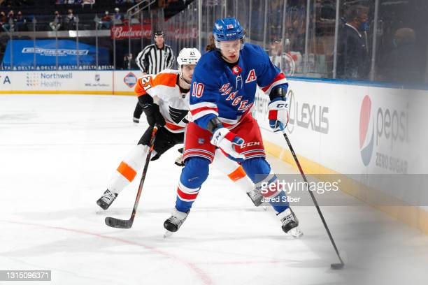 Artemi Panarin of the New York Rangers skates with the puck against Scott Laughton of the Philadelphia Flyers at Madison Square Garden on April 23,...