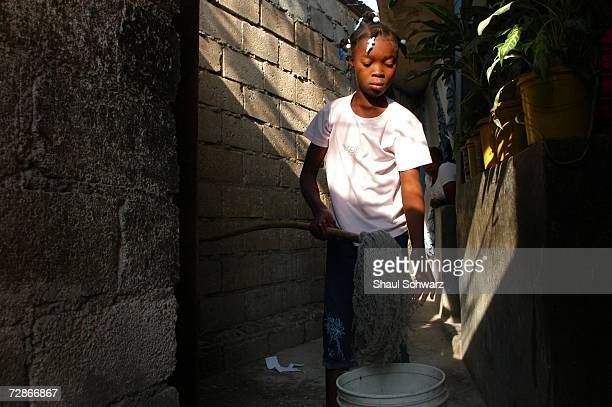 Arthemise Jean 12yearsold washes the floor of her host family's home on April 6 2005 in PortauPrince Haiti One of seven children from an extremely...