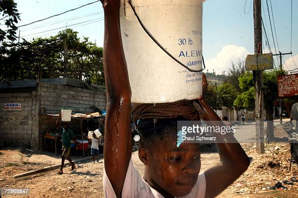 Arthemise Jean a 12yearold restavek carries water back to her host family's home on April 6 2005 in PortauPrince Haiti One of seven children from an...