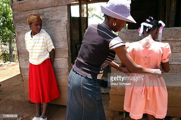 Arthemise Jean a 12yearold restavek has her dress adjusted by her host aunt as mother looks on during a rare visit to her biological family's house...
