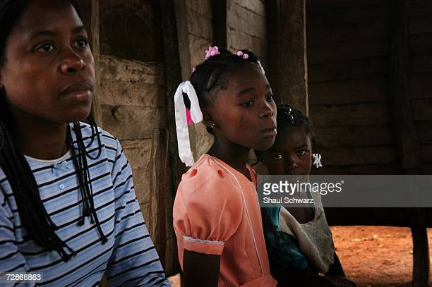Arthemise Jean a 12yearold restavek sits with her sister and Pasqual a social worker from her school on a rare visit to her biological family's house...