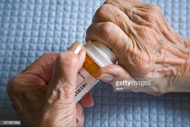 arthritis hands trying to open prescription medicine pill bottle