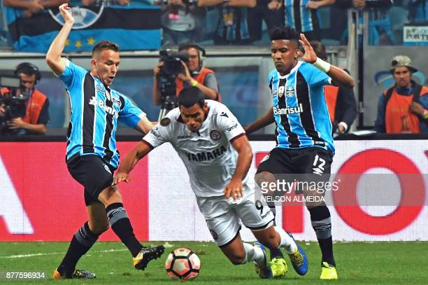 Arthur and Cortez of Brazils Gremio vie for the ball with Jose Sand of Argentina's Lanus during their Copa Libertadores 2017 first leg final match at...