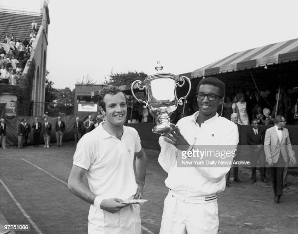 Arthur Ashe holds his US Open Trophy as Tom Okker looks on