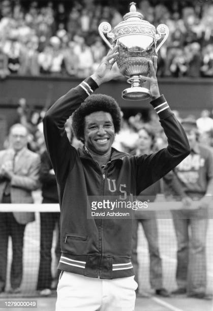 Arthur Ashe of the United States wearing his USA emblazoned Davis Cup warm-up jacket holds aloft the Gentleman's Singles Trophy on Centre Court after...