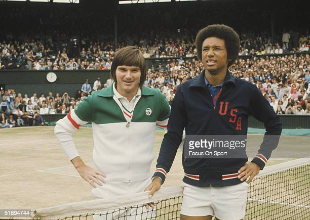Arthur Ashe poses for the camera next to Jimmy Connors at the net before a match at the Wimbledon Open in July 1975 in London England