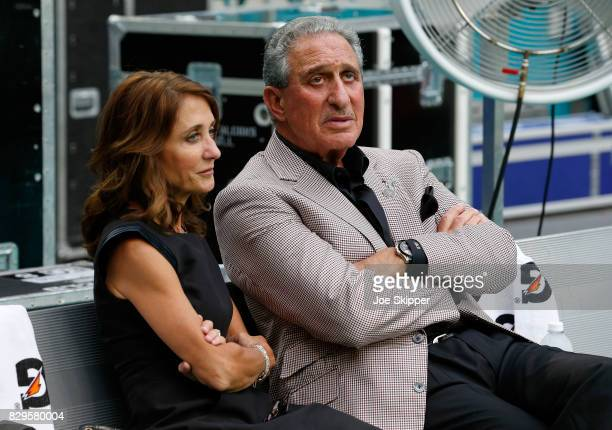Arthur Blank owner of the Atlanta Falcons sits with his wife Angela Macuga before the start of preseason play between the Falcons and the Miami...