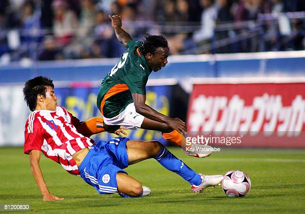 Arthur Boka of Ivory Coast and Marcelo Estigarribia of Paraguay compete for the ball during Kirin Cup match between Ivory Coast and Paraguay at...