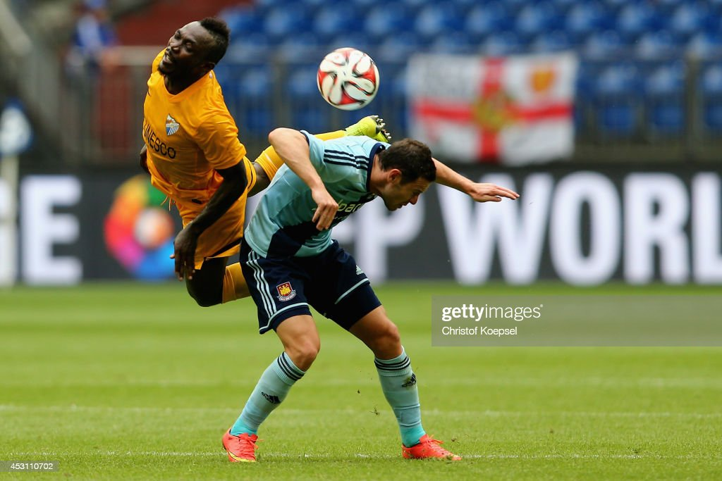 Arthur Boka of Malaga and Mauro Zarate of West Ham United (R) during the match between FC Malaga and West Ham United as part of the Schalke 04 Cup Day at Veltins-Arena on August 3, 2014 in Gelsenkirchen, Germany.
