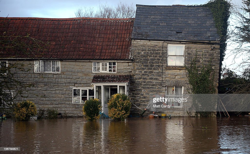 Arthur Dziewicki stands in the flood water lapping at the front door of his cottage that has been flooded close to the village of North Curry on November 21, 2012 near Taunton, England. Heavy rain overnight has brought widespread disruption to many parts of the UK particularly in the Somerset and Wiltshire and weather forecasters have warned of more wet and windy weather to come.