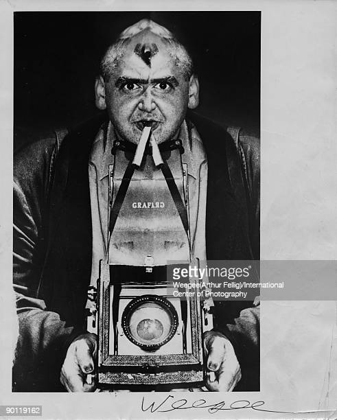 Arthur Fellig better known as the photographer Weegee in a distorted selfportrait with camera circa 1955 in New York City New York Photo by Weegee...