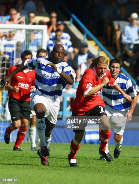 Arthur Gnohere and Michael Proctor contest the ball during the CocaCola Championship match between Queens Park Rangers and Rotherham United at Loftus...