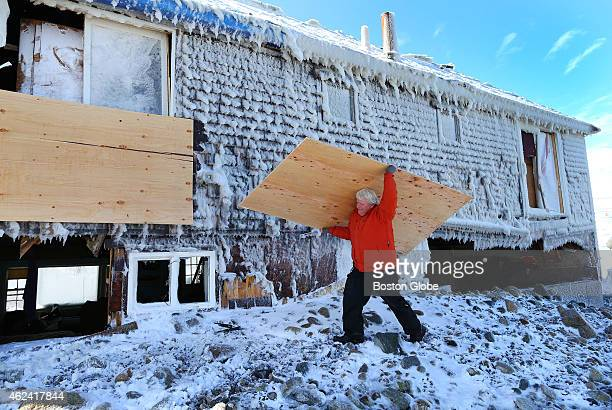 Arthur Hale carries a board as he boards up the home of his friend Timmy Mannix who was injured in the storm when a window exploded in his face...