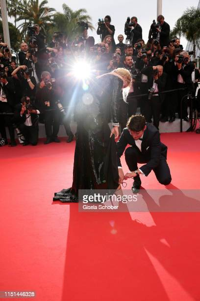 Arthur Harari ties Virginie Efira shoe before the screening of Sibyl during the 72nd annual Cannes Film Festival on May 24 2019 in Cannes France