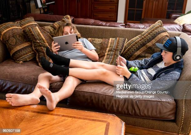 Arthur Hill left and his brother Conrad stay glued to their iPads as the lounge on the couch at their home in Tustin on Wednesday June 27 2018 Their...