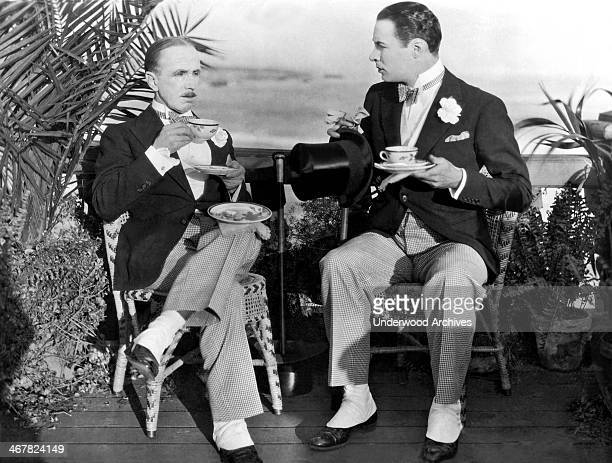 Arthur Hoyt and Rod La Rocque balance tea servings without tables in the silent film 'The Coming Of Amos' Hollywood California 1925