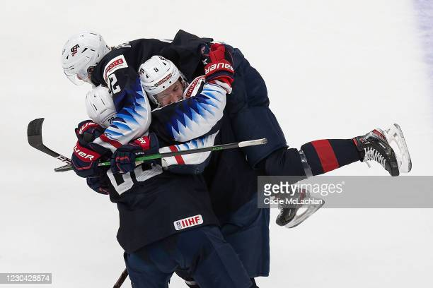 Arthur Kaliyev, Drew Helleson and Jake Sanderson of the United States celebrate the game-winning goal against Finland during the 2021 IIHF World...