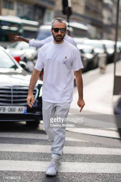 Arthur Kar wears sunglasses a Porsche white tshirt white pants sneakers outside ALYX during Paris Fashion Week Menswear Spring/Summer 2020 on June 23...