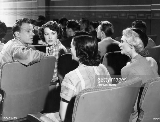 Arthur Kennedy sitting with Julie Adams in a scene from the film 'Bright Victory' 1951