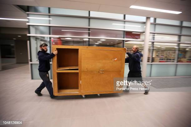 Arthur King left and Chris Post of Allen Coles Moving Systems roll a cabinet down a cooridor at the new Sanford High School on Monday Students begin...