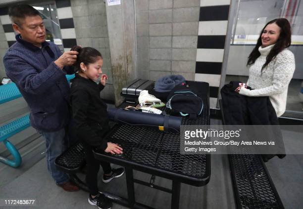 Arthur Liu left fixes his daughter Alysa«÷s hair as her coach Laura Lipetsky right looks on before practice at the Oakland Ice Center on Monday Dec...