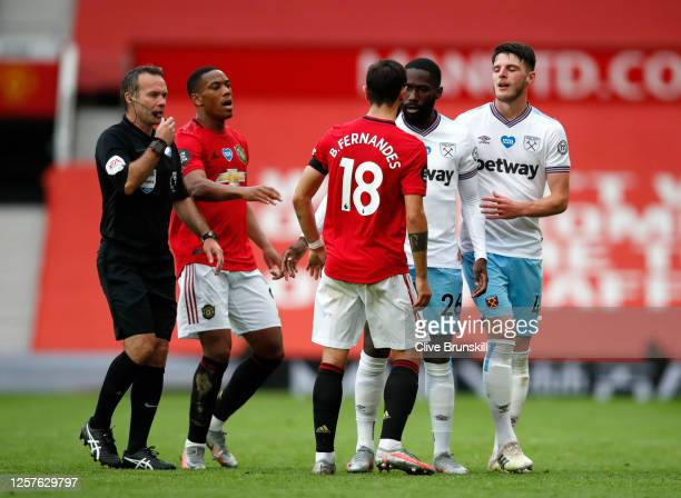 Arthur Masuaku and Declan Rice of West Ham United clash with Bruno Fernandes of Manchester United during the Premier League match between Manchester...