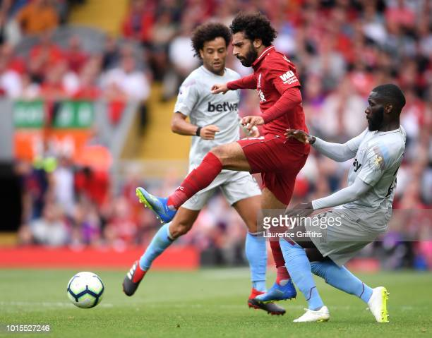 Arthur Masuaku of West Ham United challenges Mohamed Salah of Liverpool during the Premier League match between Liverpool FC and West Ham United at...