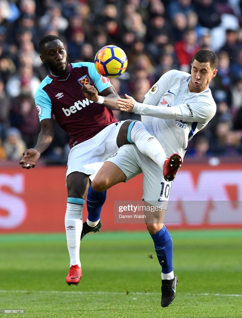 Arthur Masuaku of West Ham United is challenged by Eden Hazard of Chelsea during the Premier League match between West Ham United and Chelsea at London Stadium on December 9, 2017 in London, England.