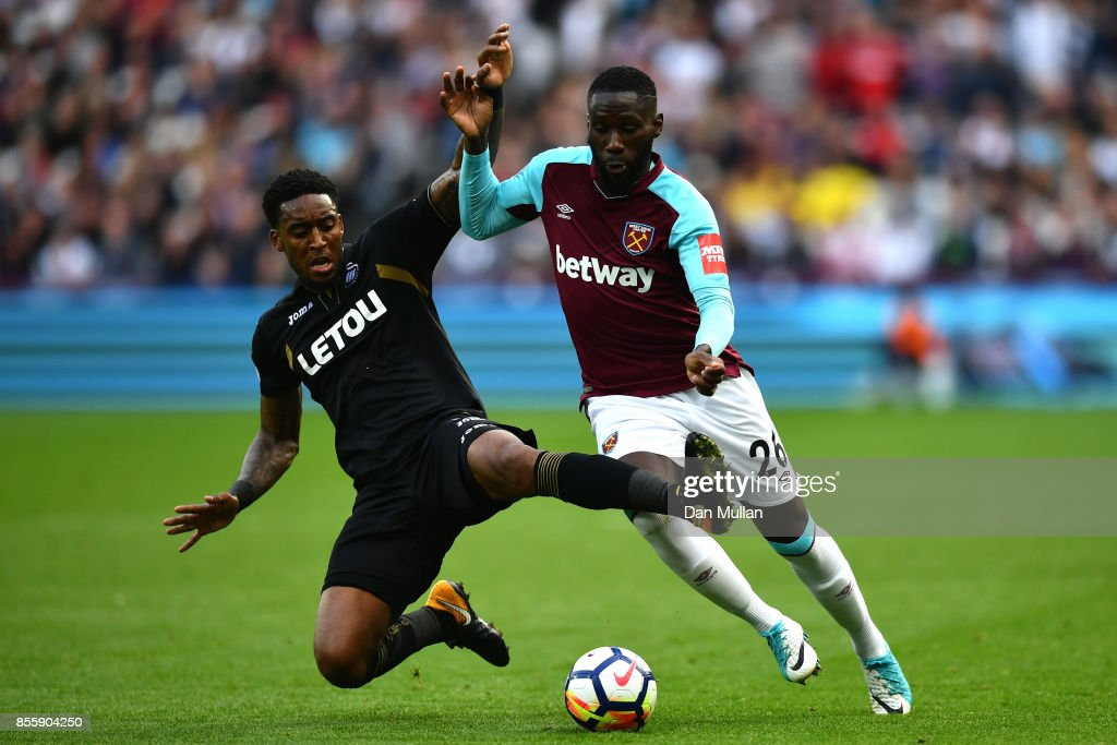Arthur Masuaku of West Ham United is tackled by Leroy Fer of Swansea City during the Premier League match between West Ham United and Swansea City at London Stadium on September 30, 2017 in London, England.