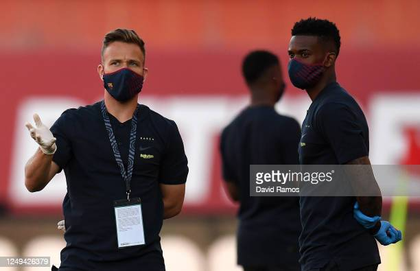Arthur Melo and Nelson Semedo of FC Barcelona wear protective masks whilst inspecting the pitch prior to the La Liga match between RCD Mallorca and...