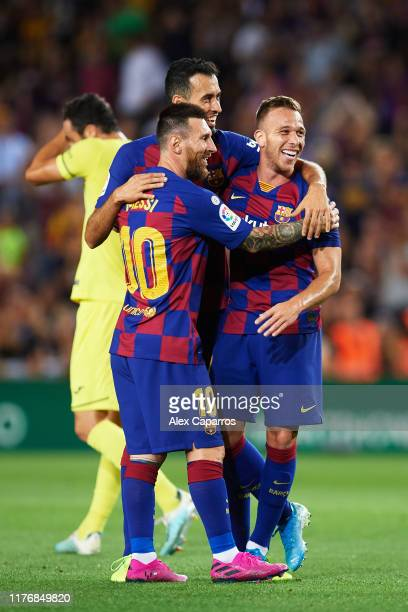 Arthur Melo of FC Barcelona celebrates with his teammates Sergio Busquets and Lionel Messi after scoring his team's second goal during the Liga match...