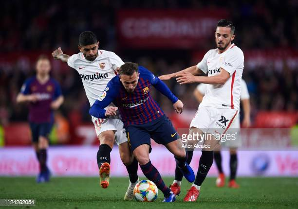 Arthur Melo of FC Barcelona competes for the ball with Ever Banega and Pablo Sarabia of Sevilla FC during the Copa del Quarter Final match between...