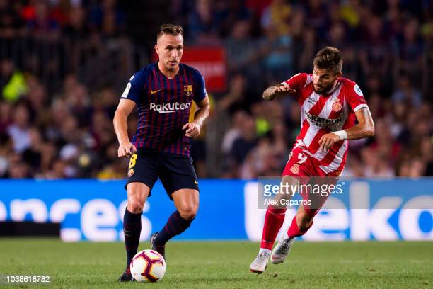 Arthur Melo of FC Barcelona controls the ball under pressure from Cristian 'Portu' of Girona FC during the La Liga match between FC Barcelona and...