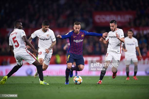 Arthur of FC Barcelona being followed by Ibrahim Amadou of Sevilla FC Ever Banega of Sevilla FC and Pablo Sarabia of Sevilla FC during the Copa del...